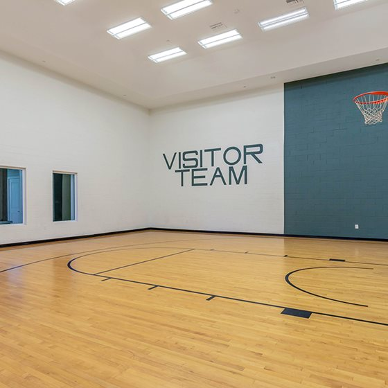 Gym with VISITOR TEAM written on the wall