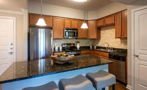 Kitchen with black counter tops and stainless steel appliances