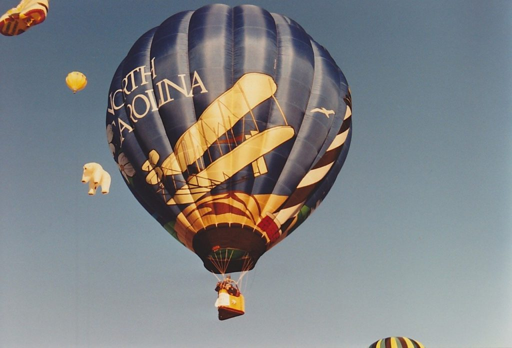 Hot Air Balloon that reads North Carolina and his an historic looking airplane on it